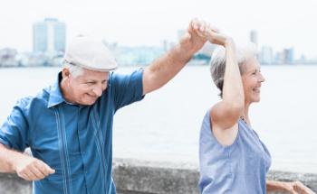 Oudere man en vrouw dansen en hebben plezier buiten in de buurt van water/ zee met een stad op de achtergrond.